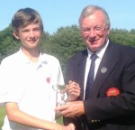 Luke receives the trophy from county president David Eccleston
